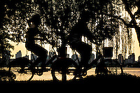 """West Lake Bicyclists"" in Hangzhou China by Art Harman. Serendipity struck when I was shooting the city skyline shortly after dawn, and these bicyclists rode by. By chance the cyclist were perfectly centered--the frame before and after were useless."