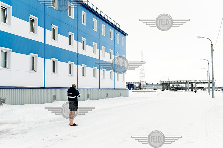 A worker smoking in front of a hostel near Obskaya railway station before his departure for a one month shift working on the Gasprom Bovanenkovo gas field.