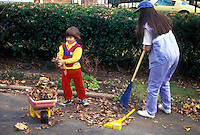 GARDEN CLEANUP with Mother and Son, little boy with toy wheelbarrow and rake, Mom raking leaves in autumn