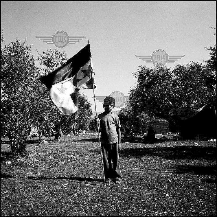Syria/Atmeh/A child refugee holding the flag of the revolution in Atmeh  village in Syria, while waiting to cross the borders and find shelter to neighborhooding Turkey.60,000 of Syrians have died since the uprising began in March 2011 and  more than 500,000 of Syrian refugees have fled the country to neighboring Turkey,Lebanon,Jordan and Iraq.Giorgos Moutafis