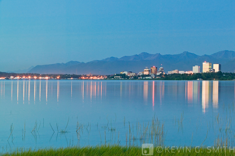 View of downtown Anchorage skyline across Knik Inlet, city reflected in the water, shot from Earthquake Park. Chugach mountains in background. summer, sunset, Anchorage Alaska.