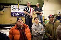 People watch Mitt Romney speak at a Romney campaign event to begin at Gilchrist Metal Fabricating in Hudson, New Hampshire, on Jan. 9, 2012.  Romney is seeking the 2012 Republican presidential nomination.