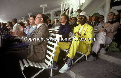 St Johns Wood, London. 1985<br /> At Lords Cricket Ground a Barbadian fan colour co-ordinates his yellow suit, with his pipe and sunglasses. Other cricket lovers dress rather more soberly  in cricket casual  wear, tweed jackets , jumpers and slacks.
