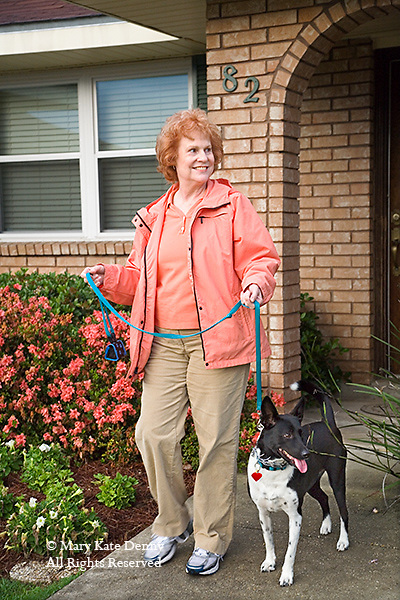 Older red headed smiling woman leaves her brick house holding the leash of her black and white dog to walk her small dog