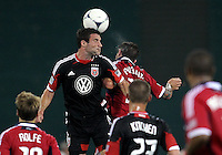 WASHINGTON, DC. - AUGUST 22, 2012:  Chris Pontius (13) of DC United up for a header against  Daniel Paladini (11) of the Chicago Fire during an MLS match at RFK Stadium, in Washington DC,  on August 22. United won 4-2.