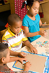 Preschool ages 3-5 two boys and a girl working   on puzzles vertical