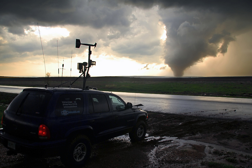 Storm spotters track a large tornado as it sweeps across the Texas Panhandle. The vehicle is equipped with instruments to take measurements such as pressure, temperature wind direction/speed and dewpoint which can be useful in studying these violent storms.