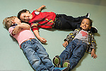 Education Preschool 2-3 year olds boys making shape on the floor with their bodies, laughing