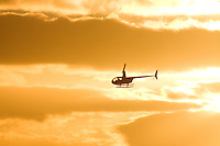 A helicopter flies over O'ahu near sunset.