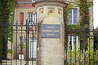 The iron gate in front of the garden and the house with a pillar with a marble plaque with the name in golden letters   at harvest time  Chateau Raymond Lafon, Meslier, Sauternes, Bordeaux, Aquitaine, Gironde, France, Europe