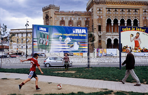 Sarajevo, Bosnia. Children playing football in front of the old library with advertising hoarding for INA petrol and oil.