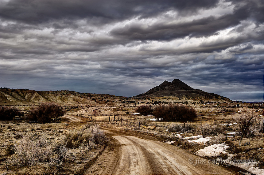 Sandoval County Road 279 where it crosses Torreon Wash in the Rio Puerco Valley with Cerro Cuate in the background under a stormy sky.