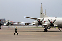 A pilot walks out onto a runway on a base in Naha city, Okinawa, Japan. Japan Maritime Self Defence Force PC3 reconnaissance planes are seen in the background. 2012