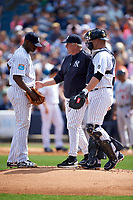 New York Yankees pitching coach Larry Rothschild (center) talks with starting pitcher Luis Severino (40) and catcher Brian McCann (34) during a Spring Training game against the Detroit Tigers on March 2, 2016 at George M. Steinbrenner Field in Tampa, Florida.  New York defeated Detroit 10-9.  (Mike Janes/Four Seam Images)