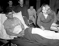 Marlene Dietrich, motion picture actress, autographs the cast on the leg of Tec 4 Earl D. McFarland of Cavider, Texas, at a United States hospital in Belgium, where she has been entertaining the GIs.  November 24, 1944. Tuttle. (Army)<br /> NARA FILE #:  111-SC-232989<br /> WAR & CONFLICT #:  758