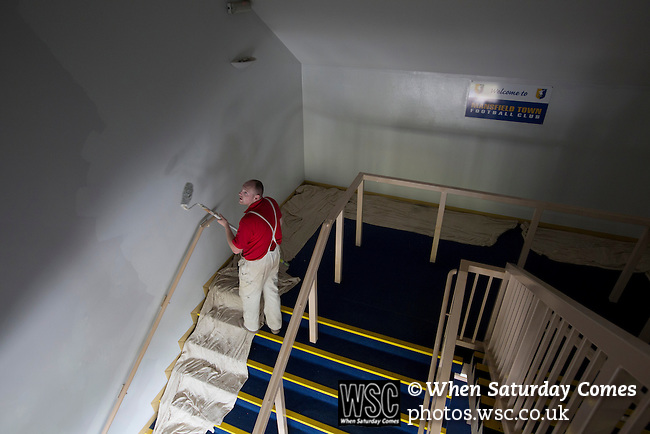 Mansfield Town Football Club Open Day, 14/07/2013. Field Mill stadium, League Two. A painter working on one of the interior stairwells at Mansfield Town's Field Mill stadium during an open day held for the club's supporters as the club get ready for the new season. Mansfield Town achieved promotion back to England's Football League by winning the Conference National in season 2012-13. Field Mill was the oldest ground in the Football League, hosting football since 1861 although some reports date it back as far as 1850, with Mansfield Town having played there since 1919. Photo by Colin McPherson.