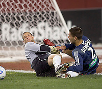Andy Gruenebaum (Columbus Crew, gray) and Clint Dempsey (NE Revolution, blue) eye the loose ball after a save. NE Revolution defeat Columbus Crew, 1-0, at Gillette Stadium and secure home field advantage in the Eastern Conference Semifinal Series on October 14, 2006.