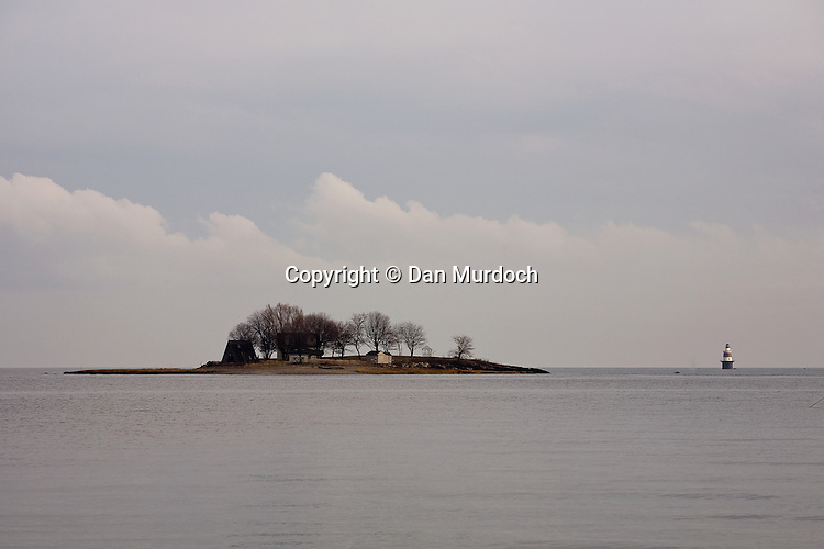 Island and lighthouse on gray day under cloudy skies