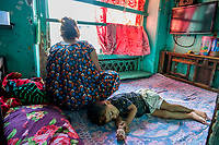 India, Maharashtra, Mumbai, Bombay, red light district. Mathura Bhavan building. A sex-worker looks out the window as her child sleeps on the bed next to her. Each year hundreds of children are born to sex-workers and while many are placed in shelters, others are raised in the brothel.