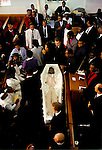 MOURNERS STANDING, & SEATED IN PEWS, WITH CORPSE IN OPEN COFFIN AT A NEW TESTAMENT CHURCH OF GOD FUNERAL SERVICE, LONDON,