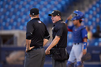 Umpires Larry Dillman Jr. (left) and Tyler Wall (right) talk between innings of an Arizona League game between the AZL Rangers and the AZL Brewers Blue on July 11, 2019 at American Family Fields of Phoenix in Phoenix, Arizona. The AZL Rangers defeated the AZL Brewers Blue 5-2. (Zachary Lucy/Four Seam Images)