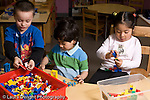 Education Preschool 3-4 year olds two boys and a girl playing separately with Legos colorful plastic bricks horizontal