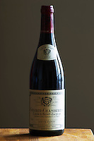 A bottle of Maison Louis Jadot Bourgogne Gevrey Chambertin Lavaux-Saint-Jacques Premier 1er Cru 2004 red burgundy wine standing on a wooden table top. Backlit backlight back light lit. gray grey background sidelit side light, Maison Louis Jadot, Beaune Côte Cote d Or Bourgogne Burgundy Burgundian France French Europe European