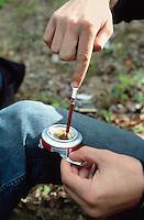 Yugoslavia. Kosovo. Pristina. Drug addiction. Heroin. Hard drug. Young man, drug addicted, prepares his daily heroin injection in Germia's forest near Pristina. © 2001 Didier Ruef