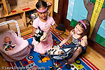 Education preschool 3-4 year olds two girls playing with dolls in strollers and puppets