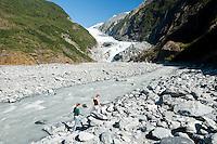 Franz Josef Glacier and tourists walking beside Waiho River - Westland National Park, West Coast