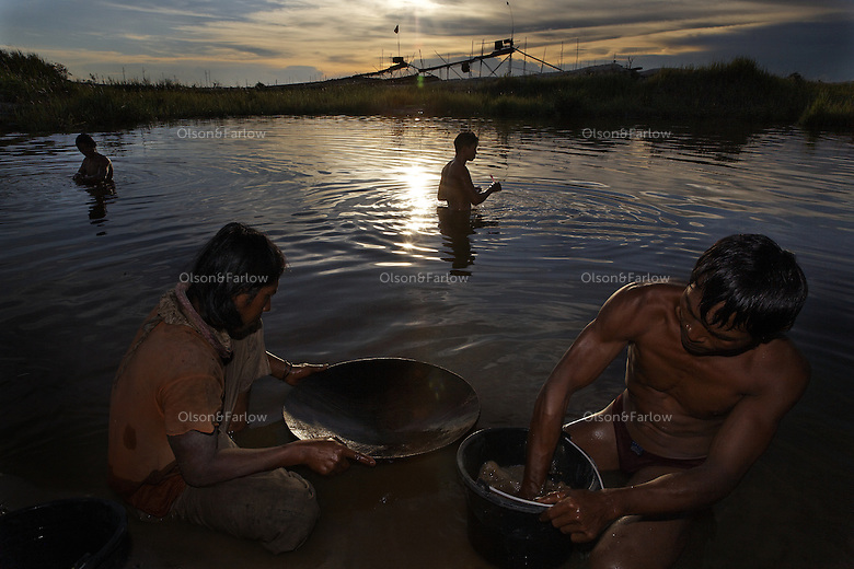 """The two guys panning with mercury in the amalgam pond are Sukardi and Suwarni--all from east Java and none of them have last names.   East Java has high unemployment and there are many migrant workers on Kalimantan (Borneo) from Java who came initially to do artisanal timber work.  The government stomped out the little guys in timber in favor of two big companies so they could control (read """"profit from"""") the industry.  So all the artisanal timber workers switched to gold. Karang Pani is a new regency established by the government--The town is only 3 years old and is support center for the artisanals--providing diesel engines, retorts to purify amalgam and other services.  The gold mining area is called Galangan and is about 11KM out of town. There are 15 retorts in Karang Pani and the mercury goes up in the smoke but then rains down on the town.  Miners test in the 1000 plus area for ppm of mercury--normal is 170 to 300 depending on how many mercury fillings you have (results of Unido testing in area).  Miners earn about $5USD a day.  E. Java is way overcrowded and the govt. has an official transmigration program over to Kalimantan.  In E. Java they can earn about 100RP a day hoeing the fields, here they can earn upwards of 30,000-60,000RP ($3-$6) a day. So it is worth it to them to camp in this area having only the water from the amalgam ponds to bath and drink.  I have many photos of people brushing their teeth or bathing next to a guy panning with a big glob of mercury."""