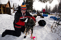 Thursday March, 2012   Volunteer veterinarian Michael Lavrone checks Justin Savidis' team shortly after his arrival at the Ophir checkpoint.   Iditarod 2012.