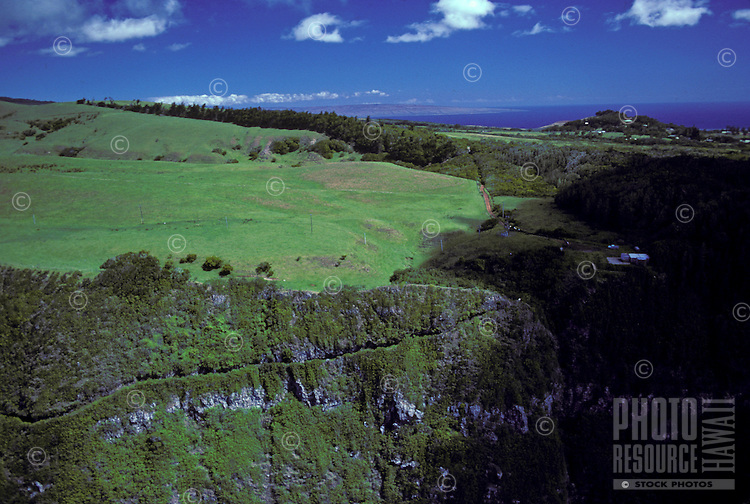 Aerial view of topside, cliffs, and switchback trail leading down to the Kalaupapa peninsula which houses the remaining population of former leprosy patients. A mule ride, taking tourists down to the pensinsula, is a popular attraction.
