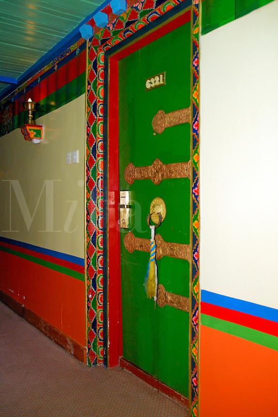 Typical Tibetan painted interior decor and door inside the Dhood Gu hotel, Lhasa, Tibet.