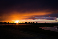 Sunset with a sunburst.   Above are dissipating storm clouds.  On the right is the San Francisco skyline.  In the foreground is San Leandro Bay and Martin Luther King Jr. Regional Shoreline, Oakland, California.