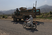 Afghan motorcyclist drives past an RG31 MRAP vehicle from RCP29 (103rd Mountain Division - Route Clearance Patrol) in the Kunar Valley near the Pakistan border.