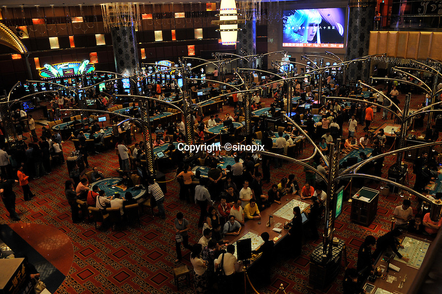 """Gamblers fill the tables in the New Lisboa Casino in Macau, 25th October 2008.  Macau is known simply as """"Vegas"""" in China. The former Potuguese colony, now a Chinese Special Administrative Region, attracts millions of Chinese gamblers annually and last year earned more gambling dollars than Las Vegas."""