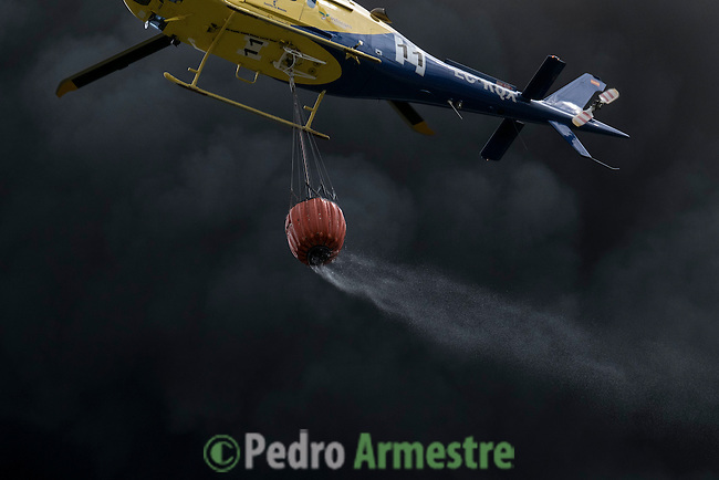 A helicopter drops water over tyres burning in an uncontrolled dump near the town of Sesena, after a fire broke out early on May 13, 2016. A huge waste ground near Madrid where millions of tyres have been dumped was on fire today, releasing a thick black cloud of toxic fumes that officials worry could harm residents nearby.  © Pedro ARMESTRE