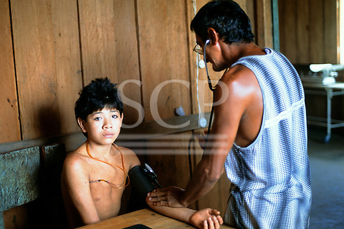 Ipixuna Village, Brazil. Child with skin disorder; Funai doctor taking blood pressure; Arawete Indians.