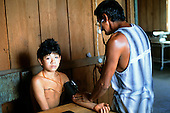 Ipixuna Village, Brazil. Child with skin disorder; Funai doctor taking blood pressure; Arawete Indians.