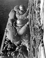 Troops are climbing down cargo net to waiting LCVP's as they land.  January 9, 1953. (Army)<br /> NARA FILE #:  111-SC-FEC-53-402<br /> WAR & CONFLICT BOOK #:  1417