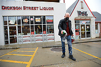 Billy Waite, owner of Dickson Street Liquor, spreads salt Wednesday, Feb. 10, 2021, outside the business as he opens for the day in the historic building where it has operated since 1964 on Dickson Street in Fayetteville. Wintry weather and freezing temperatures are expected to continue into next week. Visit nwaonline.com/210211Daily/ for today's photo gallery. <br /> (NWA Democrat-Gazette/Andy Shupe)