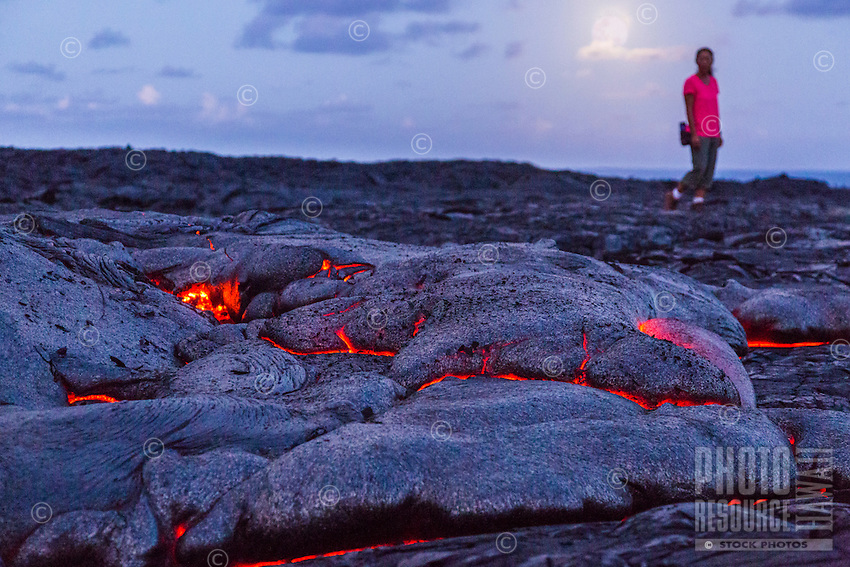 A woman walks by glowing lava under a full moon, Hawai'i Volcanoes National Park, Hawai'i Island.