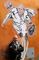 """L'artista di strada Maupal (Maurizio Pallotta) posa di fronte al disegno di Papa Francesco raffigurato come Superman, da lui realizzato ed affisso sulla parete di un palazzo del rione Borgo, nei pressi della Citta' del Vaticano, a Roma, 29 gennaio 2014.<br /> Italian street artist Maupal (Maurizio Pallotta) poses in fron of his street art mural depicting Pope Francis as Superman, and holding a bag reading """"Values"""" on a wall of the Borgo district near the Vatican, in Rome, 29 January 2014.<br /> UPDATE IMAGES PRESS/Riccardo De Luca<br /> <br /> STRICTLY ONLY FOR EDITORIAL USE"""