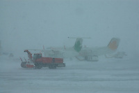 Airport during snowstorm with snow blower and commuter planes