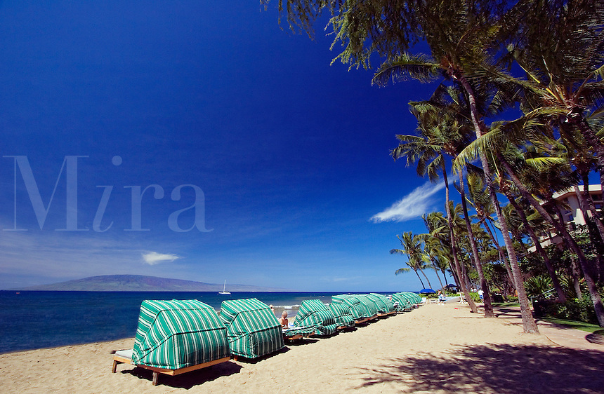 Sun cabanas on Kaanapali Beach facing the island of Lanai from Maui, Hawaii.