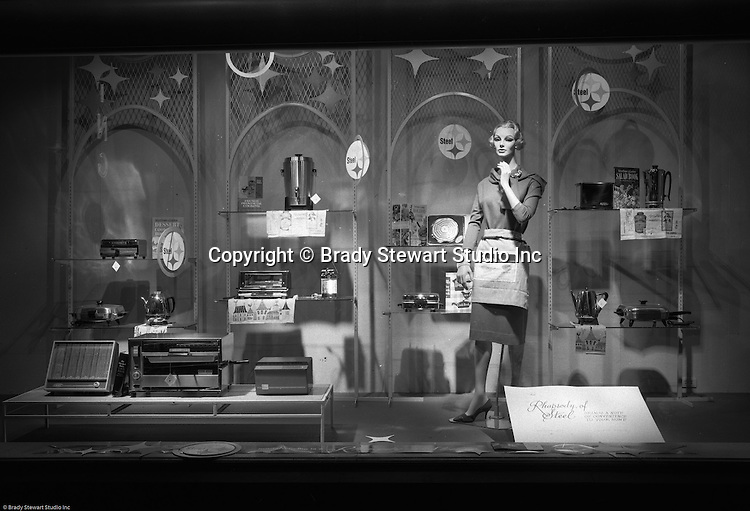 Client: US Steel<br /> Ad Agency: US Steel Marketing<br /> Contact:<br /> Product: Steel displays and fixtures and consumer products made from steel.<br /> Location: Hornes Department Store in downtown Pittsburgh<br /> <br /> View of Christmas window display at Horne's department store in downtown Pittsburgh. Woman manikin dressed up for kitchen duty and surrounded by steel appliances for the home.  The display was part of the Rhapsody of Steel promotion at Horne's.  US Steel launched an awareness campaign of all the current uses of steel in everyday products.  During this time, ALCOA Aluminum Company of America also headquartered in Pittsburgh, was aggressively competing to enter markets where US  steel companies traditionally dominated market share. Examples included beer and food Cans, appliances, automobile parts, children's toys/bicycles, and more.