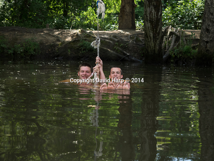Happy as a pair of river otters, Luke Kemp, right, and Ricky Cecil do what generations have done to pass the a summer day.