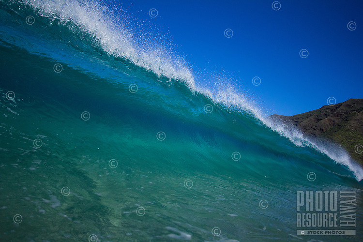 Blue and Green breaking wave at Makua Beach on the West Side of O'ahu.
