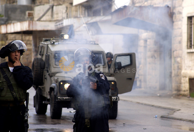 An Israeli policeman fires a tear gas canister during clashes with Palestinian protesters at a demonstration against the closure of Shuhada street to Palestinians, in the West Bank city of Hebron February 24, 2012. Some 200 protesters, including foreign and Israeli activists, gathered on Friday marking the 18th anniversary of the closure of the street, which was closed by the Israeli army in 1994 following the Hebron mosque massacre by Baruch Goldstein, an Israeli settler, who went on a rampage inside Al Ibrahimi Mosque, killing 29 Palestinian worshippers. Photo by Mamoun Wazwaz